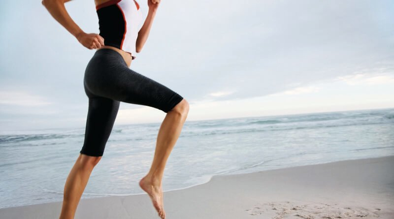 Mid section of a female athlete doing practice jog on the sea shore